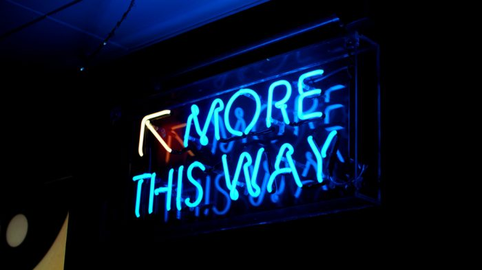 A,Bright,Blue,Fluorescent,'more,This,Way',Neon,Sign,With