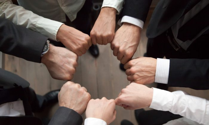 Business,Team,Or,Partners,Put,Fists,In,Circle,As,Concept