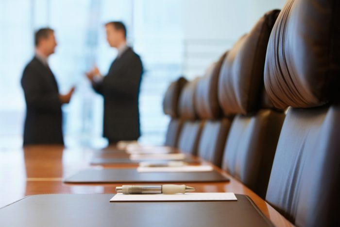 Side,View,Of,Two,Blurred,Businessmen,Talking,In,Conference,Room